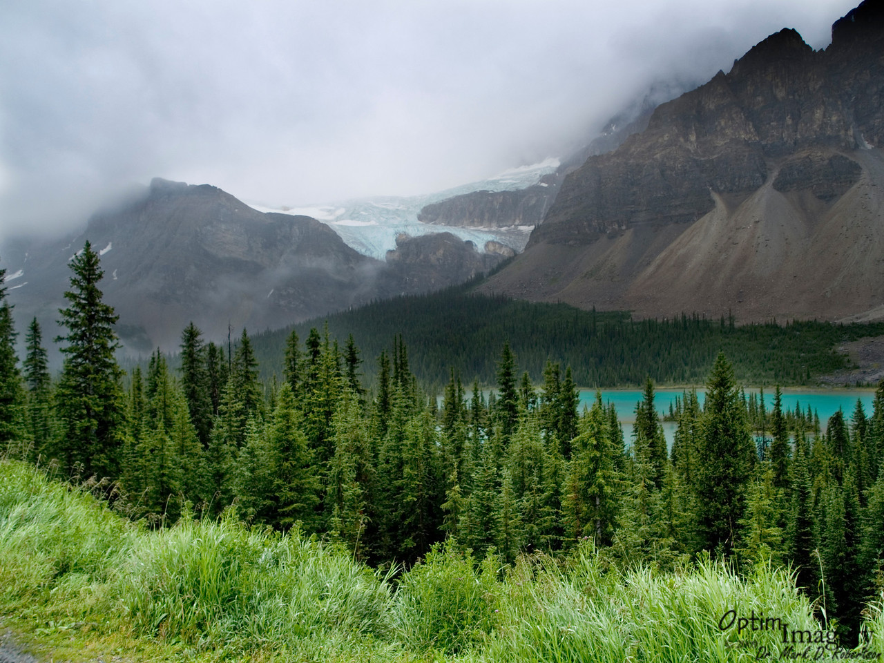 """After a nice, relaxing night in Banff, we headed north along the Icefields Parkway.  Here we are looking to the west, across the Bow River, to Crowfoot Glacier hanging up on the cliff.  I remember the first time I saw glaciers, and how mesmerized I was at the radiant, turquoise glow.  I had expected them to be white, but they are not.  More on that later.  This poor crow has lost one toe.  When it was named, it had an extension below the lower one you see here.  That """"toe"""" has receded over the years since then.  However, the ice cliff you see at the lower left portion of the glacier is still 50 m (160 feet) tall."""