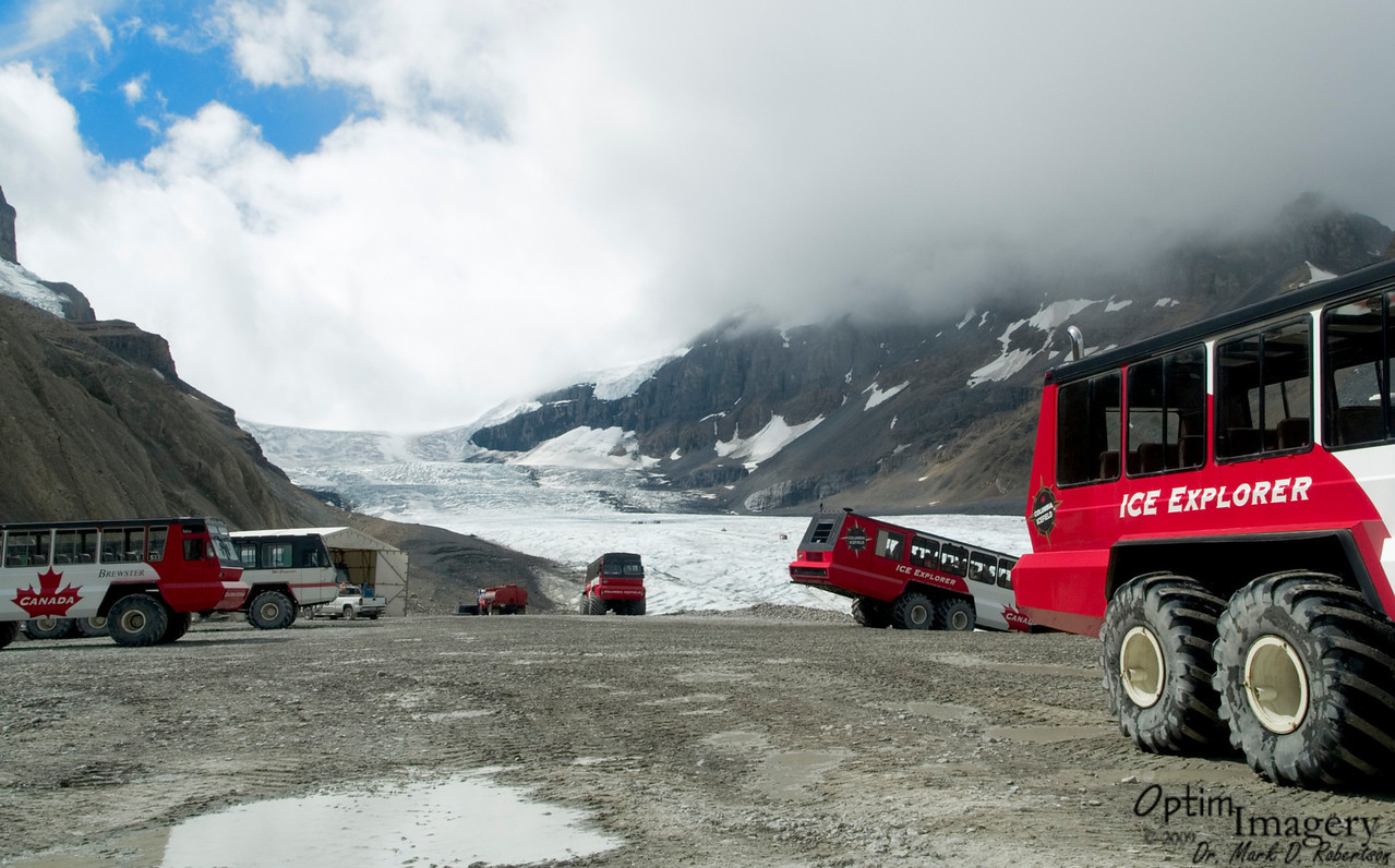 Back at the snow bus lot.  You can see that the next group of tourists is starting down the road to Athabasca.  You can also see a couple of snow busses on the glacier (look just behind the one heading down the hill).  If you look closely, you can even see there there are 2 parked down on the ice  in the distance where we were walking earlier (in that little darker area).