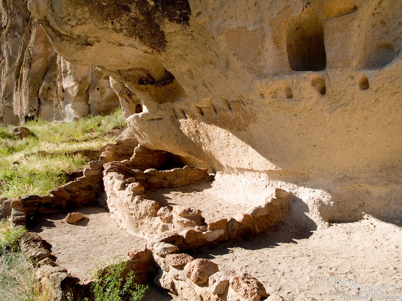 The small holes in the straight row (called viga holes) were scraped out of the cliff for insertion of wooden beams.  These beams then supported the roofs for the buildings (the bases of which you see here).  So the small cave opening you see here would have opened onto the roof or into the second story.