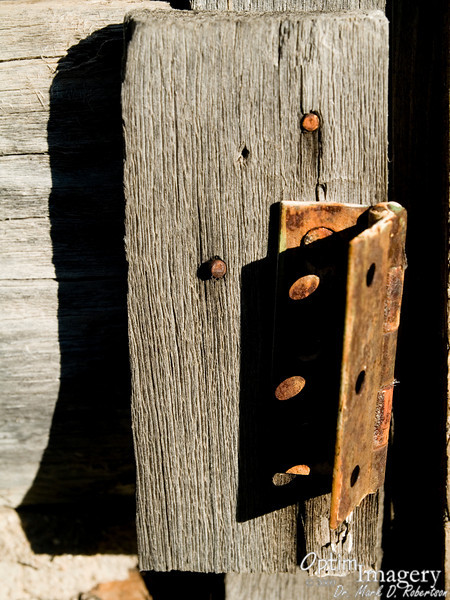 Old hinge on a door frame at the old cabin.  I couldn't resist the evening shadow.  My original intent was to do this in B&W, but I just loved the contrast of the  rusty color of the hinge and nails on the old gray, weathered wood.