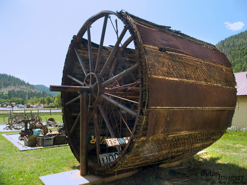 """This separator wheel was suspended in a large vat containing water slurry / gold amalgam suspension.  There were 2 layers of heavy canvas covering the wheel, with air blown between the layers, causing the outer layer to """"balloon outward.""""  As the wheel rotated, the gold mixture formed a coating on the external canvas.  This amalgam was then scraped off the wheel by a long, fixed blade."""