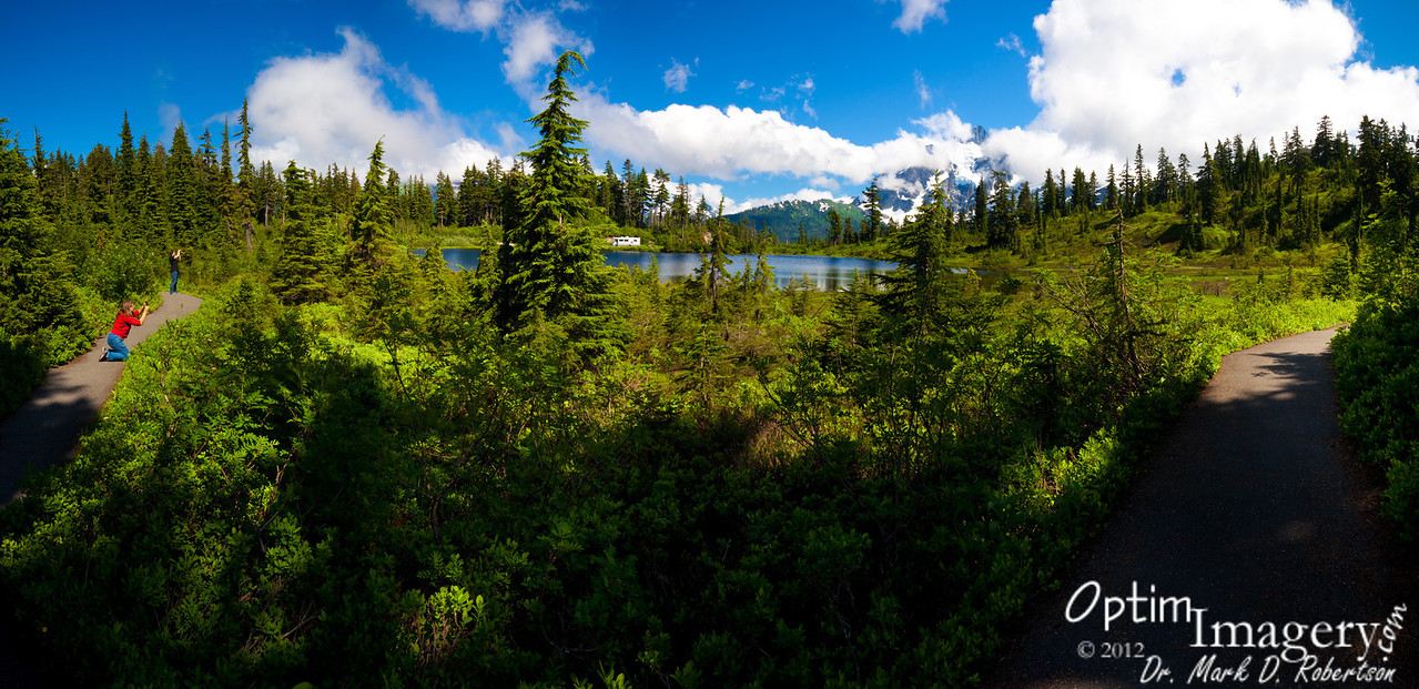 14-photo panorama of Bev and Bri photographing Picture Lake and Mount Shuksan.  Original size gives lots of detail.