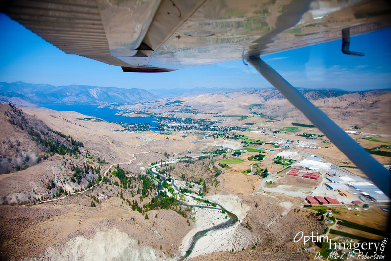 From above the Columbia, looking west over Lake Chelan.  Chelan River (according to Wikipedia the shortest river in the state of Washington, flowing from the largest natural lake in WA) and apple sheds in the foreground.