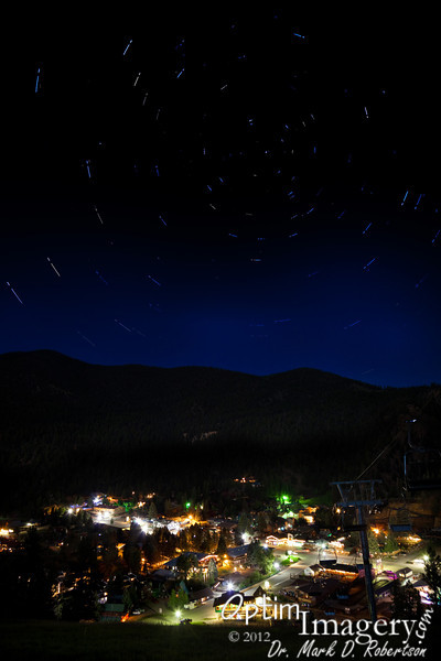 The town of Red River at night, from up on the main ski run, looking north (Polaris, or the North Star, is the one nearest the center of the circle of star trails).  I was up on the slope for more than 2 hours taking all the shots which went into this photo.  My fear of the possibility of encountering a bear at night finally got the best of me and I decided to head back down to safety (I had been wanting much longer star trails than these, but would have needed more time for that).  On my way down, I did indeed see a bear toward the bottom of the slope to our left,which happened to be exactly the direction I was walking.  I quickly changed course and headed more to the right and safely got back into town.  <br /> <br /> As I was walking to the condominium we were staying in that night, there was a large SUV stopped at an intersection and the folks therein motioned me to come over.  I saw that the SUV was filled with college-aged students, and they asked me if I had seen the TWO bears up on the slope.  When I affirmed that I had seen one, they told me that they had been watching two of them up there (from the safety of their SUV), and they had been a bit concerned about the fellow coming down the slope (me).  <br /> <br /> I felt very fortunate to have gotten this shot to show to you.  Somehow the fact that the star trails aren't as long as I wanted just didn't seem all that important once I had that little bit of bear information.<br /> <br /> In case you are interested, I took 43 photos, ranging from 1/5 sec to 3 minutes to combine for this photo.  The star trails show how far our Earth rotates in 17 minutes.  Over 2 hours on the slope with at least 2 bears roaming around, and then a couple of hours getting all of this combined in Photoshop so that I can present to you this one picture.  Can you recommend a good psychiatrist for me?