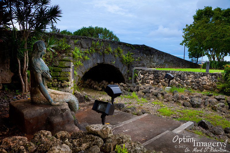 "SIRENA AT SAN ANTONIO BRIDGE<br /> <br /> This bridge was built in 1800 over the Hagatna River.  After WWII the river was diverted, but the bridge left in place.  It now is a nice historic landmark over a dry ditch.<br /> <br /> The story of Sirena:<br />  <br /> Guam's legendary mermaid, Sirena, lived in Agana during Spanish times near the Minondo River where fresh spring waters dividing the city of Agana met the ocean at the river's mouth (Bicana) not so far from the site of the statue above. She loved the water and was known to swim whenever she could steal a moment from her chores to satisfy her greatest pleasure.<br /> <br /> One fateful day, Sirena's mother sent her to get coconut shells to be used as coal for the iron. Oblivious to time and duty, Sirena couldn't resist the refreshing river. There she swam while her mother called impatiently. Sirena's godmother happened to be visiting, and as her mother angrily cursed her daughter with the words, ""Since Sirena loves the water more than anything, she should become a fish"", her Nina (godmother) quickly interjected, ""leave the part of her that belongs to me"".<br /> <br /> Unknown to mother, godmother, family and friends, Sirena was never to return home again, for feeling unusual sensations as she swam, she soon discovered that from the waist down she had become part fish.<br /> <br /> Her mother, regretful of her curse, could not undo the outcome of fate. Bidding her loved ones farewell, Sirena swam out into the Pacific. Since her disappearance, seafarers have reported seeing her in different parts of the world. According to legend, she can only be caught with a net of human hair."