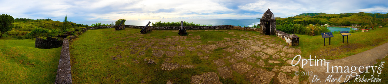 27-photo panorama from Fort Soledad.  San Dionicio Church is visible across Umatac Bay to your right.  A small part of Umatac Bridge is barely visible between the furthest-to-your-right bench and little coconut tree (near the extreme right of the photo).
