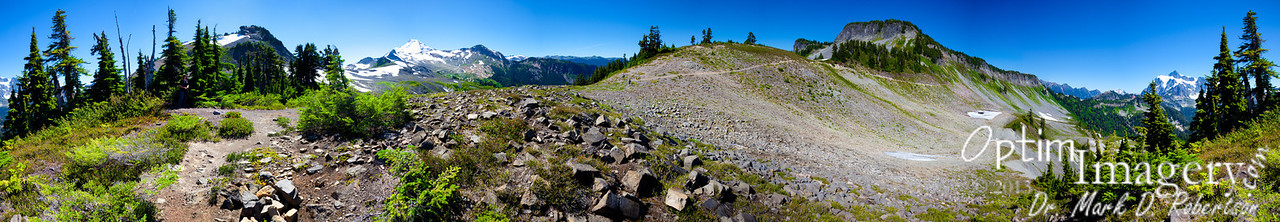 """360-degree panorama made up of 25 photos.  Mount Suksan is to your right, and you can follow the trail over the slope (where the previous few photos were taken from) and see Mount Baker to your left from the center of the photo.  Notice that the 2 or 3 trees on the extreme left are the same ones on the extreme right.  Hover your mouse over the photo and then click """"Original"""" from the pop-out menu.  Give it a little time to load and you will have a full size rendering of this.  It will not fit on your screen, so you will need to use the scroll bars to your right and bottom of your screen to navigate.  If you click on the photo it will return you to the Smug Mug Gallery format.  Can you find Bri?  How about Zac?  They are both in here."""