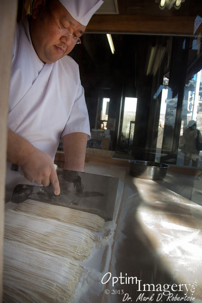 After rolling it out, folding it, and re-rolling it out several times, he then cuts the dough into these noodles.