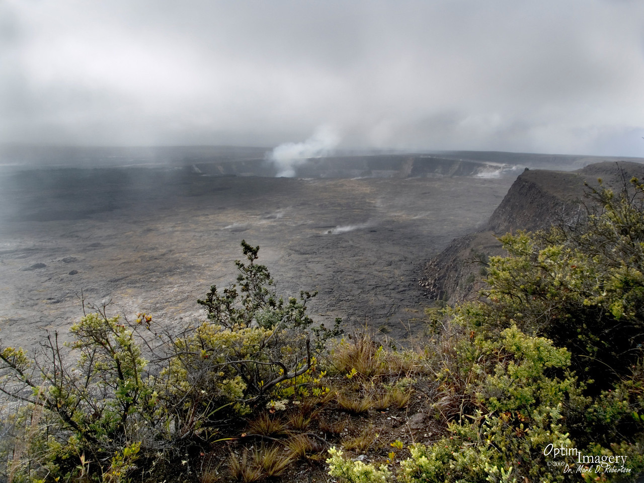 Kilauea Caldera.  As recently as the late 1800's, the bottom was twice as deep as it is today (about 500 feet today) and one could see lakes and fountains of molten lava churning.  It solidified roughly in the configuration seen today in about 1905.  However, there has been occasional seepage of lava through fissures, forming lava flows as recently as the 1970's.  The hole you see in the distance (with the large steam plume) is Halema'uma'u, the central crater of the caldera.  As recently as 1924, it contained a molten lava lake.  Now, the rock is thought to be solid down to a depth of about 2 miles below the surface.