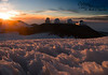 """Hawaiian snow in the reddish light of the setting sun in the foreground.  Poli'ahu, the cinder cone to your left, is considered to be both the embodiment of and the home of Poli'ahu, the snow goddess.  The observatories, from left to right, are as follows:  Subaru ( <a href=""""http://subarutelescope.org/"""">http://subarutelescope.org/</a> ), Japan's national telescope.  At 26.9 feet in diameter, its mirror is one of the largest single-piece telescope mirrors made.  It took three years to manufacture the blank, and another four years to polish it and prepare it for mounting.  The unusual shape was chosen because computer simulations indicated that it would reduce the amount of turbulent outside air entering the enclosure.  The central two domes are the Keck 1 and Keck 2 (  <a href=""""http://keckobservatory.org/"""">http://keckobservatory.org/</a> ).  With mirrors of 33 feet in diameter, these are the largest visible light (and infrared) telescopes in the world.  Unlike the Subaru, however, these mirrors are each made up of 36 hexagonal segments, with each of these individually controlled to keep alignment within 4 nanometers (about 1/25,000 the thickness of a human hair).  When used together, resolution can be equivalent to what would be possible with a mirror 279 feet in diameter!  Each of the 700,000 cubic foot domes stands 8 stories tall.  The smaller one to your right is the NASA Infrared Telescope Facility (NASA IRTF) (  <a href=""""http://irtfweb.ifa.hawaii.edu/"""">http://irtfweb.ifa.hawaii.edu/</a>  ).  It has a 10 foot diameter mirror and is used primarily to gather information of use to NASA space programs."""