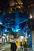 Contained in the blue drum at the bottom of the telescope structure is an 8.2 meter (27 foot) mirror, with a thickness of 7.9 inches, weight of 25.1 tons, and mean surface error of 1/5,000,000 inch.