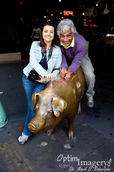 As Olga feeds her, mario rides on the back of the 550-pound bronze pig named Rachel.  The unofficial mascot of Pike Market, Rachel raises $6,000 to $9,000 per year in a combination of many different world currencies.  The funds are used to maintain the public market.<br /> <br /> Nice size piggy bank.