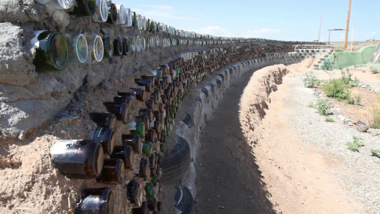 """According to their website (see   <a href=""""http://www.earthship.com/"""">http://www.earthship.com/</a>  ), an Earthship is """"a radically sustainable home made of recyclable materials.""""  Keep in mind that the second part of this video shows a construction site.  There is a nearby neighborhood of maybe 10 or so of these structures which are finished and currently inhabited -- which looks much nicer and more liveable. I did not take photos or videos there, however, because there was a sign with a rather strong message that those who lived there would prefer folks to stay away unless invited.  That did slightly surprise me, since I usually find the types of folks who are attracted to these things to be very inviting.  However, I can't blame them, and respecting their privacy seemed more important than did getting another photo or two."""