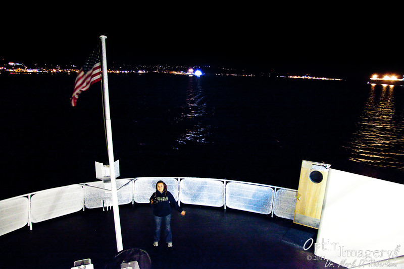 The lights of Port Angeles become smaller and dimmer in the distance as we sail under a nearly-full moon.