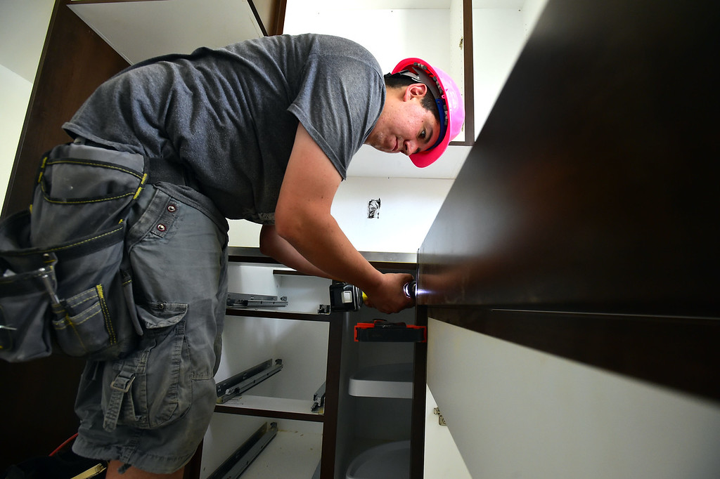 . Gene Vigil of Tharp Cabinets works on a handicap accessible sink at one of Thistle\'s affordable housing units under renovation  on 20th Street in Boulder on Thursday.  For more photos go to dailycamera.com Paul Aiken Staff Photographer June 14, 2018