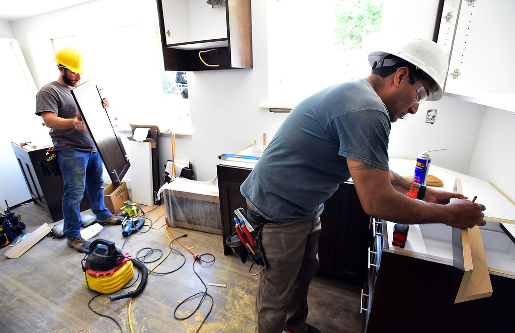 . Shane Carpenter, left, and Isidoro Almaguer, of Tharp Cabinets work at one of Thistle\'s affordable housing units under renovation on 20th Street in Boulder on Thursday.  For more photos go to dailycamera.com Paul Aiken Staff Photographer June 14, 2018