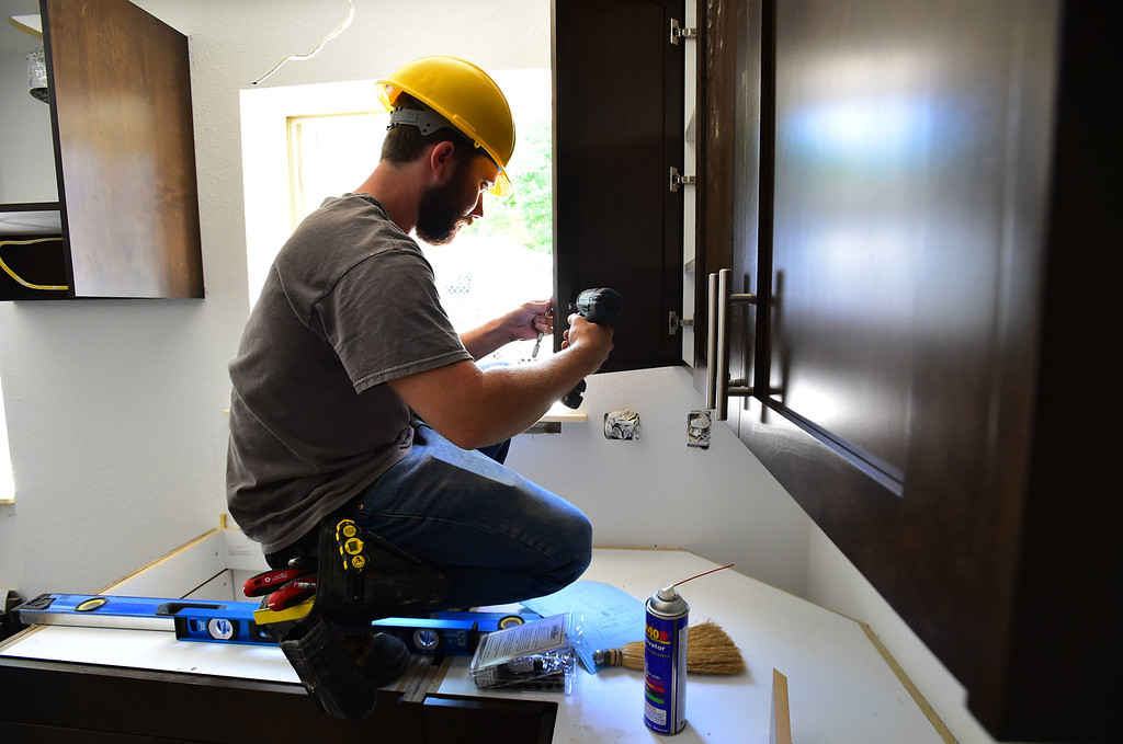 . Shane Carpenter of Tharp Cabinets works at one of Thistle\'s affordable housing units under renovation on 20th Street in Boulder on Thursday.  For more photos go to dailycamera.com Paul Aiken Staff Photographer June 14, 2018