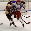 Tewksbury Memorial High School hockey player Tommy Craig nails Concord Carlisle High School player Owen Bailey as they fight for the puck. SUN/JOHN LOVE