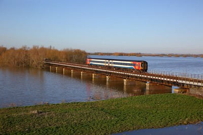 158865 on the 1L08 1240 Nottingham to Norwich crosses the Hundred foot drain - Ouse Washes at Pymoor such of Manea on the 19th January 2020