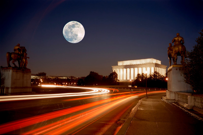 MOON OVER THE LINCOLN MEMORIAL, FRAMED BY THE ART OF WAR STATUES AND TRAFFIC TRAILS.