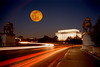 ORANGE MOON OVER THE LINCOLN MEMORIAL, FRAMED BY THE ART OF WAR STATUES AND TRAFFIC TRAILS.
