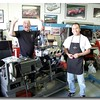 """One of the few pictures of the dyno when installed at Bob Alder's shop in Denver.  This picture taken in April of 2005 shows  Bill Bradford and Steve Estrada declaring a victory on a fresh Twin-Cam engine prepared for Bob Alder's Russell-Alexis Formula car.  There was a  """"victory""""  celebration because Bill swore he would never do another twin-cam, but did prepare this last one as a favor to Bob.  He was super glad to see it pass muster on the dyno and to never have to do another one."""