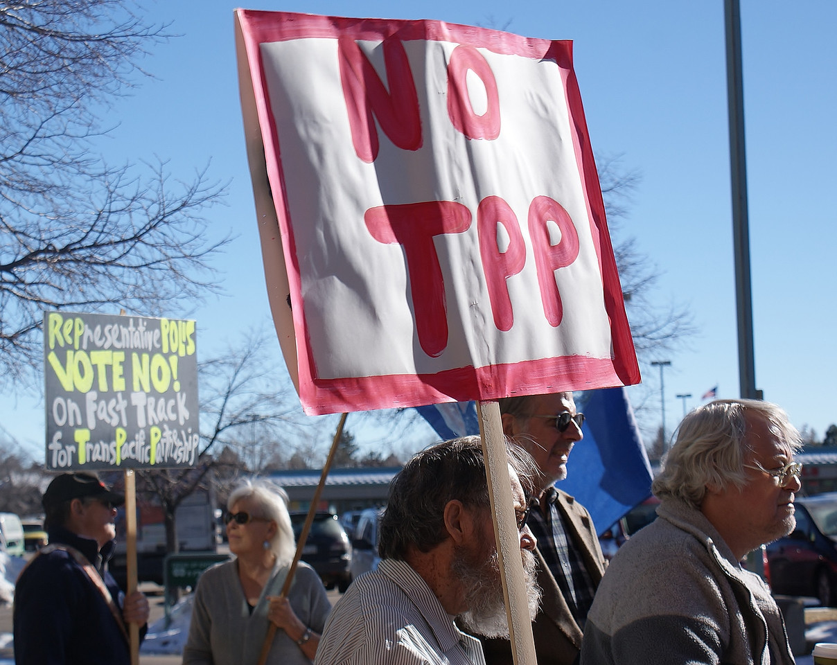 Opponents of the TPP (Trans Pacific Partnership)demonstrate outside the district office of Rep Jared Polis in Boulder, Co.