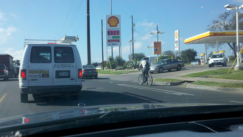 CyclistAtGasStationExit  Do you feel sorry for the vehicles leaving the gas station?  They have to wait for the cyclist to approach their lane --whatever that is--One of these days we will be able to get a photo of those guys turning left.  (We are heading North on South Congress approaching overpass at Ben White Blvd.  Yes we are making a point to avoid I35 and Mopac (metadata 11/2/12 @12:34 pm.) At least we documented the price of gasoline on that day.