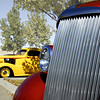 At the foreground is the grille of a 1937 Chevrolet Sedan. The yellow car is a 1937 Chevrolet Coupe with an engine souped up for drag racing.