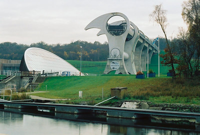 FALKIRK WHEEL AND GLASS FRONT OBSERVATION HOUSE With Gift Shop and Dining Area. The Wheel is loading a caisson from the upper canal preparing for descent to the lower pond and eventually through two locks to the lower canal.