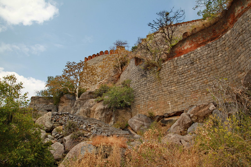 "Gingee Fort or Senji Fort (also known as Chenji, Jinji or Senchi) in Tamil Nadu, India is one of the surviving forts in Tamil Nadu, India. It lies in Villupuram District, 160 kilometres (99 mi) from the state capital, Chennai, and is close to the Union Territory of Puducherry. The fort is so fortified, that Shivaji, the Maratha king, ranked it as the ""most impregnable fortress in India"" and it was called the ""Troy of the East"" by the British. The nearest town with a railway station is Tindivanam and the nearest airport is Chennai (Madras), located 150 kilometres (93 mi) away.  Originally the site of a small fort built by the Chola dynasty during the 9th century AD, Gingee Fort was modified by Kurumbar during the 13th century. As per one account, the fort was built duirng the 15–16th century by the Nayaks, the lietunants of the Vijayanagara Empire and who later became independent kings. The fort passed to the Marathas under the leadership of Shivaji in 1677 AD, Bijapur sultans, the Moghuls, Carnatic Nawabs, French and the British in 1761. The fort is closely associated with Raja Tej Singh, who unsuccessfully revolted against the Nawab of Arcot and eventually lost his life in a battle.  The Gingee Fort complex is on three hillocks: Krishnagiri to the north, Rajagiri to the west and Chandrayandurg to the southeast. The three hills together constitute a fort complex, each having a separate and self-contained citadel. The fort walls are 13 km (8.1 mi) and the three hills are connected by walls enclosing an area of 11 square kilometres (4.2 sq mi).[1] It was built at a height of 800 feet (240 m) and protected by a 80 feet (24 m) wide moat. The complex has a seven-storeyed Kalyana Mahal (marriage hall), granaries, prison cells, and a temple dedicated to its presiding Hindu goddess called Chenjiamman. The fortifications contain a sacred pond known as Aanaikulam. On the top of the hillock, there are minor fortifications.[1] The fort, in modern times, is maintained and administered by the Archaeological Survey of India. The fort is one of the prominent tourist destinations in Villupuram district."