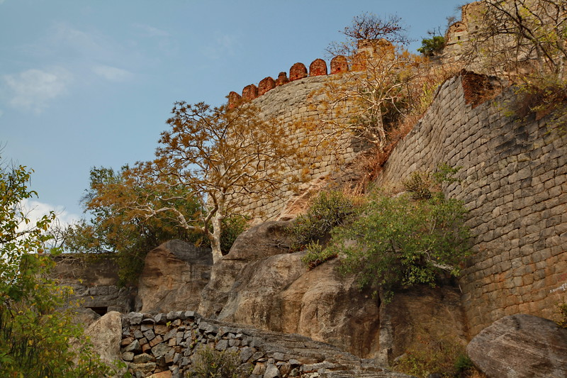 """Gingee Fort or Senji Fort (also known as Chenji, Jinji or Senchi) in Tamil Nadu, India is one of the surviving forts in Tamil Nadu, India. It lies in Villupuram District, 160 kilometres (99 mi) from the state capital, Chennai, and is close to the Union Territory of Puducherry. The fort is so fortified, that Shivaji, the Maratha king, ranked it as the """"most impregnable fortress in India"""" and it was called the """"Troy of the East"""" by the British. The nearest town with a railway station is Tindivanam and the nearest airport is Chennai (Madras), located 150 kilometres (93 mi) away.  Originally the site of a small fort built by the Chola dynasty during the 9th century AD, Gingee Fort was modified by Kurumbar during the 13th century. As per one account, the fort was built duirng the 15–16th century by the Nayaks, the lietunants of the Vijayanagara Empire and who later became independent kings. The fort passed to the Marathas under the leadership of Shivaji in 1677 AD, Bijapur sultans, the Moghuls, Carnatic Nawabs, French and the British in 1761. The fort is closely associated with Raja Tej Singh, who unsuccessfully revolted against the Nawab of Arcot and eventually lost his life in a battle.  The Gingee Fort complex is on three hillocks: Krishnagiri to the north, Rajagiri to the west and Chandrayandurg to the southeast. The three hills together constitute a fort complex, each having a separate and self-contained citadel. The fort walls are 13 km (8.1 mi) and the three hills are connected by walls enclosing an area of 11 square kilometres (4.2 sq mi).[1] It was built at a height of 800 feet (240 m) and protected by a 80 feet (24 m) wide moat. The complex has a seven-storeyed Kalyana Mahal (marriage hall), granaries, prison cells, and a temple dedicated to its presiding Hindu goddess called Chenjiamman. The fortifications contain a sacred pond known as Aanaikulam. On the top of the hillock, there are minor fortifications.[1] The fort, in modern times, is maintained and admini"""