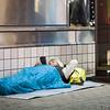 A homeless man enjoying mobile technology close to Shibuya crossing.