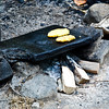 Cooking cornbread on an open fire.