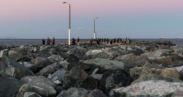 160730 1753 - A crowd of people walking along the breakwater at Mackay.