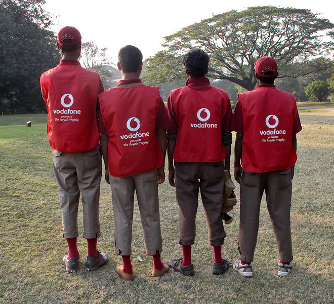 Royal Calcutta caddies advertise for the Royals Tournament Sponsor Vodafone