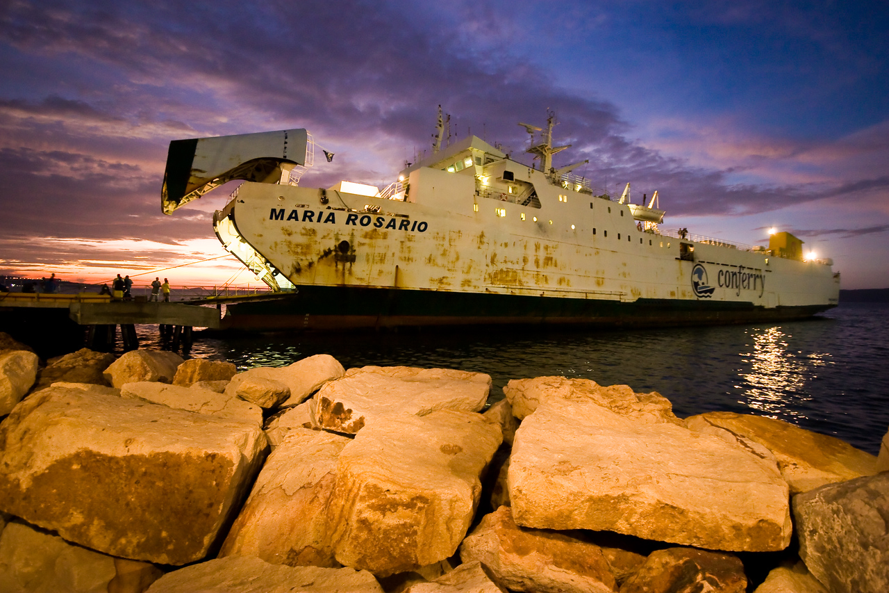 Taken while standing in the queue to board this ship.  <br /> <br /> The foreground light on the rocks is coming from fluorescents overhead hanging from a covered walkway that isn't in the shot.  The ship illumination is from the parking lot lights behind me.  And the sunset...well, I think we all know where that comes from.<br /> <br /> This is one of my favorites from this trip.<br /> <br /> Location: Puerto La Cruz, Venezuela<br /> <br /> Lens used: 10-22mm f3.5-4.5
