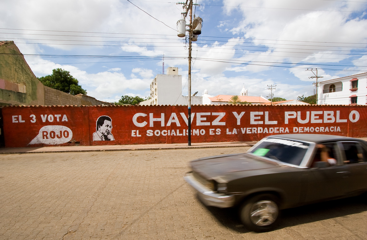 By using a narrow aperture, I was able to slow down the shutter enough to blur the passing car.  I thought that made for a nice foreground for the Hugo Chavez political banner behind.<br /> <br /> Location: Coro, Venezuela<br /> <br /> Lens used: 10-22mm f3.5-4.5
