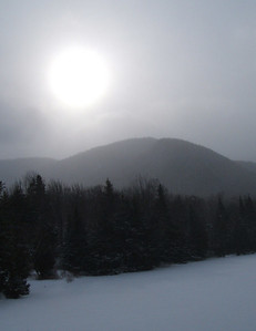 The sun above Marcy Dam on a socked-in morning.