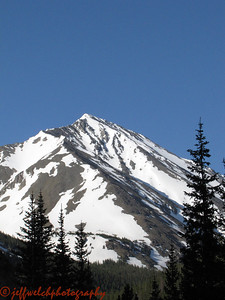 Our journey started with dropping a car at the bottom of the Grizzly Gulch 4WD road.  Just over a week earlier, Mike and I snowmobiled to the same spot.  The snow is melted now.  This view of Torreys' northeast face (the Emperor) is a fine way to begin the morning.