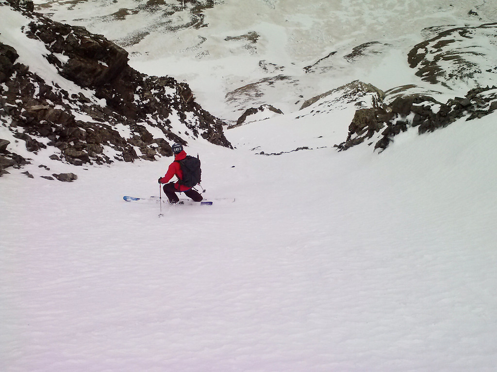 After a quick summit, Hans descends the steep pitch above large cliffs.
