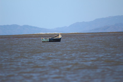 Lone Boat Anchored in River Mouth