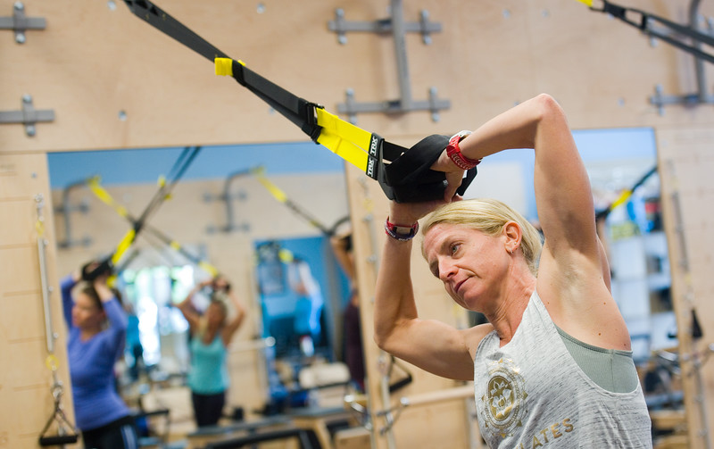 "Instructor Erica Ruge uses the TRX suspension training system to exemplify the next step in the workout of the TRX/Reformer Fusion class at Club Pilates in Longmont on Wednesday.<br /> For more photos go to  <a href=""http://www.dailycamera.com"">http://www.dailycamera.com</a><br /> (Autumn Parry/Staff Photographer)<br /> May 18, 2016"