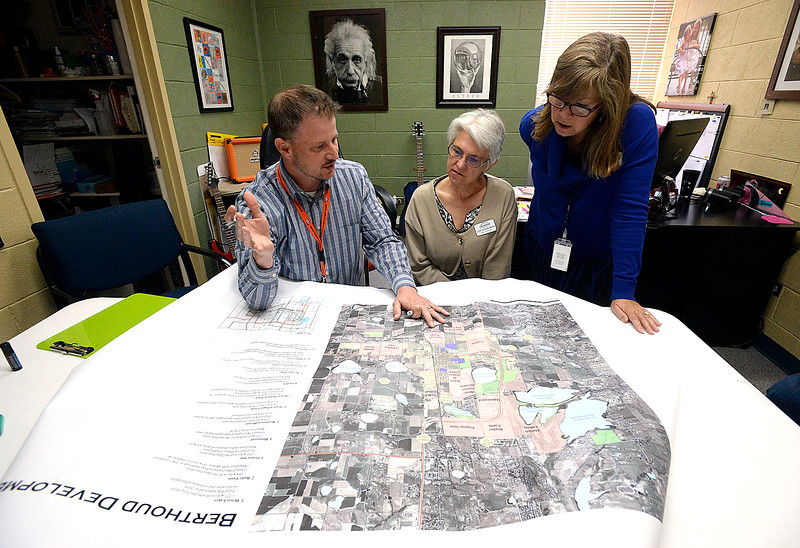 Ivy Stockwell Elementary School Principal Rick Bowles, left, refers to a map of development in the area as he speaks with Thompson School District board members Lori Hvizda Ward, center, and Pam Howard on Thursday, April 26, 2018, as he talks about the challenges they face with growth at the school in Berthoud. (Photo by Jenny Sparks/Loveland Reporter-Herald)