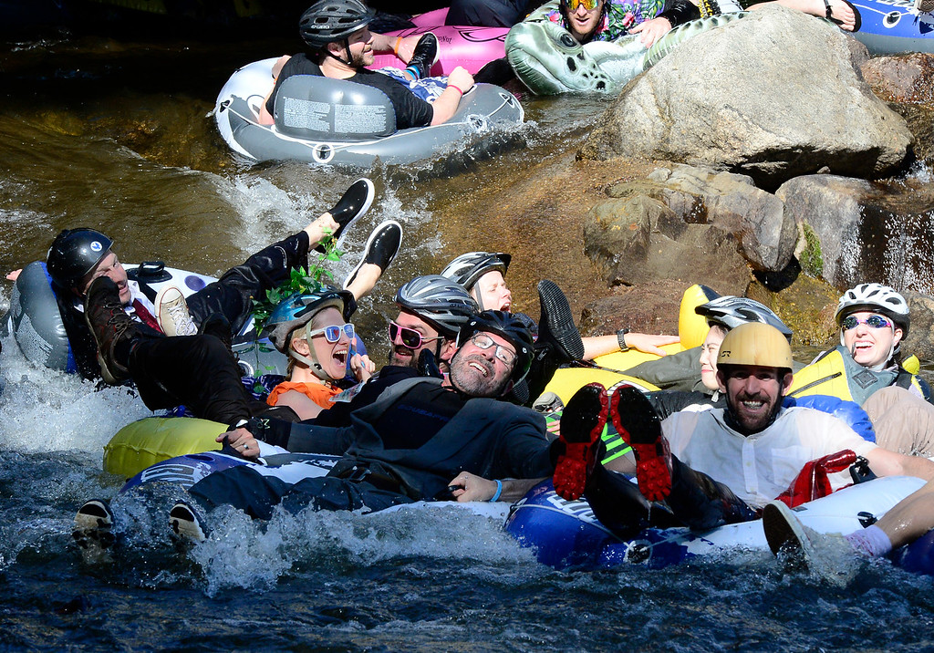 . James Potach hangs on to his group of tubers on Boulder Creek near the finish of the 11th Annual Tube to Work Day on Wednesday morning.  Paul Aiken Staff Photographer July 11 2018
