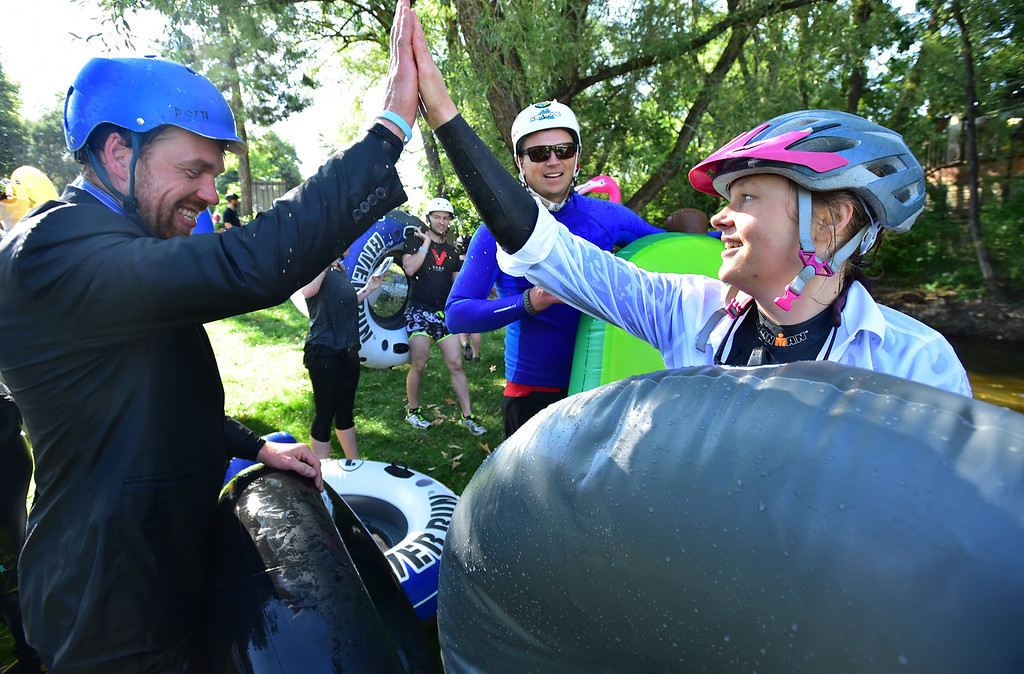 . Jeff Woodward, left, and Devron Hobbs high five at the finish at Central Park during the 11th Annual Tube to Work Day on Wednesday morning. Fellow tuber Dan Campbell looks on from the middle. Paul Aiken Staff Photographer July 11 2018