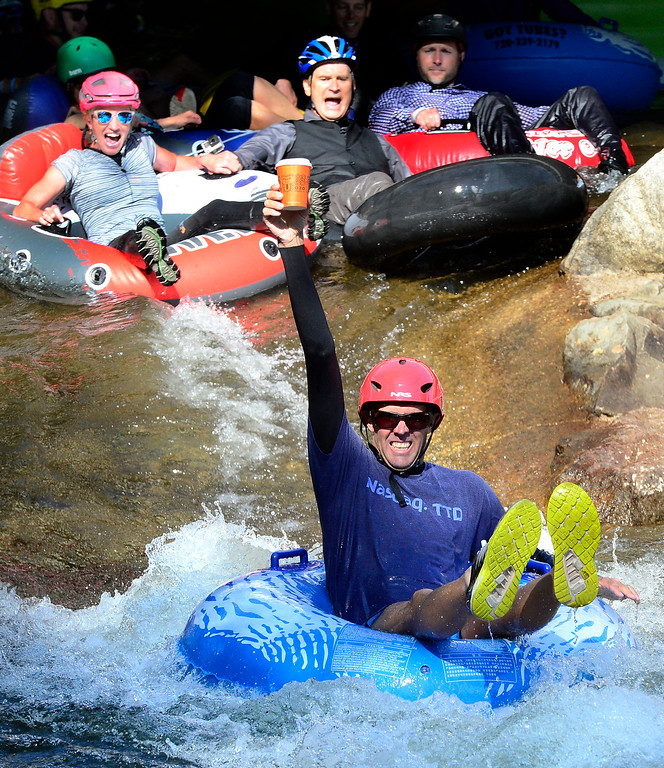 . Mike Davis hangs onto his coffee as he hits the last rapid on Boulder Creek near the finish of the 11th Annual Tube to Work Day on Wednesday morning.  Paul Aiken Staff Photographer July 11 2018