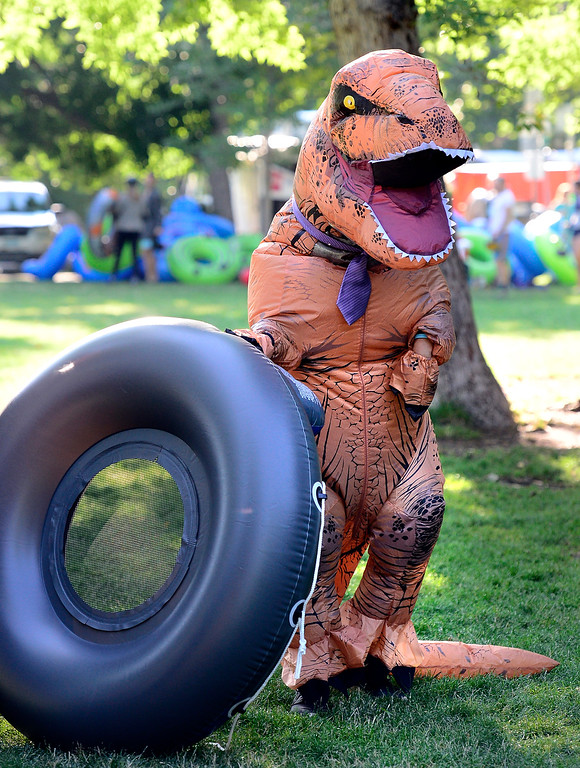 . David Lee, dressed as a T-Rex dinosaur gets prepared at Eben G. Fine Park for the 11th Annual Tube to Work Day on Boulder Creek on Wednesday morning.  Paul Aiken Staff Photographer July 11 2018