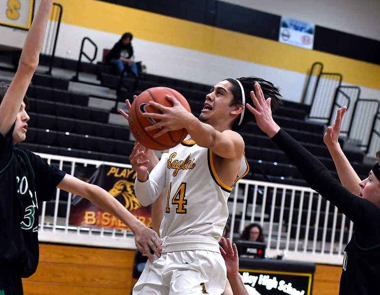 Thompson Valley's #14 Julian Espinoza goes up for a shot as Niwot's #1 Jackson Kolakowski and #32 Cameron Carlson try to block during their game Thursday, Feb. 9, 2017, at Thompson Valley High School in Loveland.  (Photo By Logan O'Brien/ Loveland Reporter-Herald)