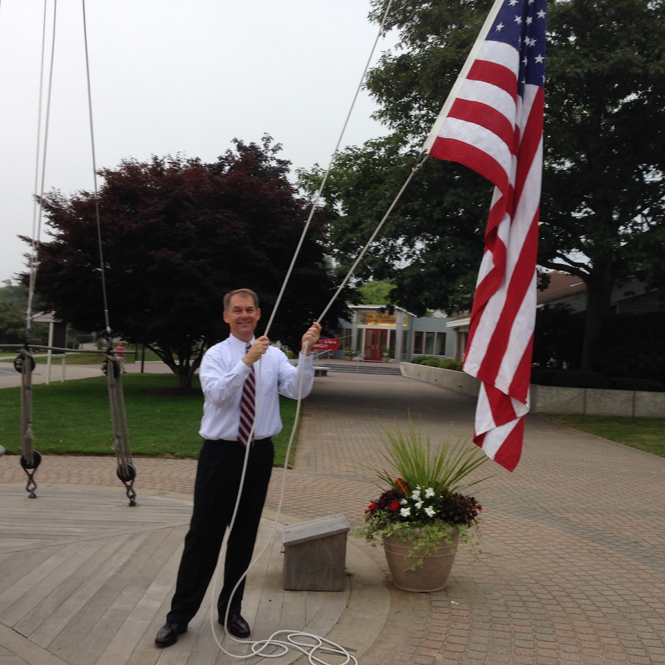 Mr. Quirk, Head of School, hoisting the flag in preparation for the arrival of our new and returning students on Registration Day.